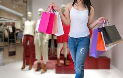 Kvinnlign går händer som rymmer ferie för shoppingpåsar arkivbild