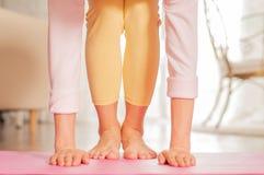 kvinnlign hands ben Kvinna som hemma gör yoga på den matta konditionen royaltyfri foto
