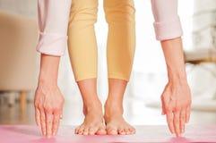 kvinnlign hands ben Kvinna som hemma g?r yoga p? den matta konditionen arkivfoton