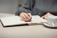 Kvinnlign har anmärkningar för kaffeavbrott och handstili dagbok eller notepad; arkivfoto