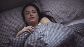 Kvinnlign i hennes 20-tal vaknar upp i morgonen i en säng, flicka sträcker sig, når hon har sovit lager videofilmer