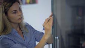 Kvinnlign klibbar legitimationshandlingar på den glass dörren som skriver viktiga frågor lager videofilmer