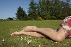 Kvinnlign lägger benen på ryggen att koppla av på gräsgräsmatta Royaltyfri Bild