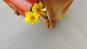 Kvinnlign lägger benen på ryggen handväskan med blommor Arkivbilder