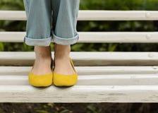 Kvinnlign lägger benen på ryggen i jeans och gulingskor på en vit bänk royaltyfri fotografi