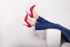 Kvinnlign lägger benen på ryggen i jeans och röda höga häl Arkivbild