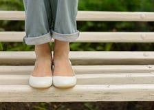 Kvinnlign lägger benen på ryggen i jeans och vitskor på en vit bänk Royaltyfri Fotografi