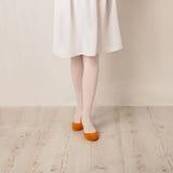 Kvinnlign lägger benen på ryggen i vit strumpbyxor, kjol, och balett sänker på en vit b Arkivbilder