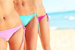 Kvinnlign lägger benen på ryggen och buktar i bikini på stranden royaltyfria bilder