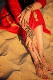 Kvinnlign lägger benen på ryggen, och händer med hennatatueringen på stranden sandpapprar bakgrund Royaltyfri Foto