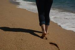 Kvinnlign lägger benen på ryggen rörande framåtriktat längs kusten Royaltyfri Bild