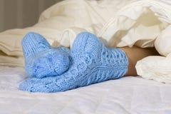 Kvinnlign lägger benen på ryggen under filten på sängen i de blåa woolen sockorna kallt väder, avkoppling, vilar hemmet arkivbilder