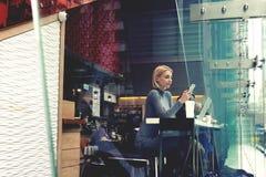 Kvinnlign läser modenyheterna i internet via mobiltelefonen, medan vilar hennes beställning i coffee shop arkivfoto