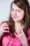 Kvinnlign manipulerar porträtteringen med hennes stetoskop Arkivbilder