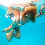 Kvinnlign med ögon öppnar undervattens- i simbassäng Arkivbild