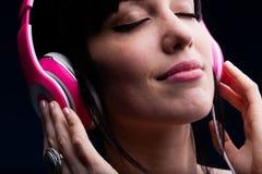 Kvinnlign med stängda ögon och grinar genom att använda hörlurar royaltyfri foto