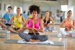 Kvinnlign mediterar i grupp, och koppla av i lotusblomma posera Arkivbild