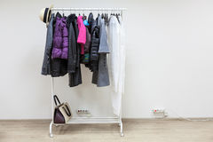 Kvinnlign och manlig svartvit outerwear som hänger på golv, rack Arkivbilder