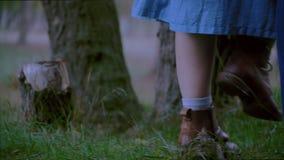 Kvinnlign och mannen lägger benen på ryggen i jeans och kängor som går på grässlutet upp stock video