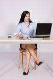 Kvinnlign poserar bak ett skrivbord i kontoret Royaltyfria Foton