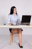 Kvinnlign poserar bak ett skrivbord i kontoret Arkivfoton