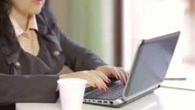 Kvinnlign räcker arbete på en bärbar dator tät inomhus fotografi för bakgrund upp white Långsam mo
