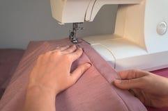 Kvinnlign räcker arbete på symaskinen Arkivfoto