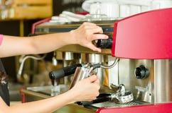 Kvinnlign räcker arbete som fungerar den industriella kaffebryggaren som ångar mjölkar i metallbehållare Royaltyfri Fotografi