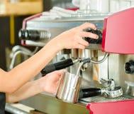 Kvinnlign räcker arbete som fungerar den industriella kaffebryggaren som ångar mjölkar i metallbehållare Royaltyfri Bild
