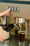 Kvinnlign räcker arbete som fungerar den industriella kaffebryggaren som häller espressoskottet Arkivfoton