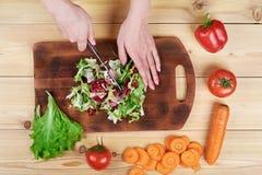 Kvinnlign räcker att hugga av grön sallad som lagar mat grönsaksallad på träbakgrund arkivfoton