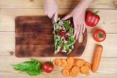 Kvinnlign räcker att hugga av grön sallad som lagar mat grönsaksallad på träbakgrund arkivbilder