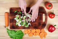Kvinnlign räcker att hugga av grön sallad som lagar mat grönsaksallad på träbakgrund royaltyfri fotografi