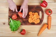 Kvinnlign räcker att hugga av grön sallad som lagar mat grönsaksallad på träbakgrund arkivfoto