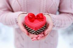 Kvinnlign räcker att rymma en gåvaask formad av hjärta Den valentindagen och julkortet royaltyfri bild