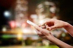 Kvinnlign räcker att rymma en mobiltelefon (smartphone) med tuchscreen i natt Arkivfoto