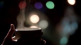 Kvinnlign räcker att rymma en råna av varmt te stock video