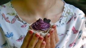 Kvinnlign räcker att rymma en Violet Small Cupcake Outdoors Decorated med liten hjärta för choklad Mat och sötsaker Smakligt mål arkivfilmer