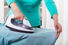 Kvinnlign räcker att stryka en skjorta Royaltyfri Fotografi