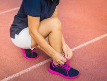 Kvinnlign räcker band av skosnöret på rinnande skor för övning ru arkivfoton