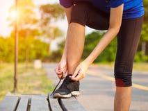 Kvinnlign räcker band av skosnöret på rinnande skor för övning ru fotografering för bildbyråer