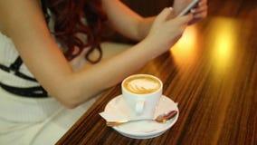 Kvinnlign räcker closeupen med telefonen och koppen kaffe Den unga kvinnan skriver meddelandet på hennes telefon arkivfilmer