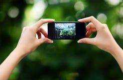 Kvinnlign räcker danandefotoet med smartphonen Arkivbilder