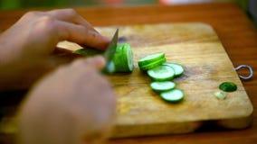 Kvinnlign räcker den bitande gurkan på träbräde lager videofilmer