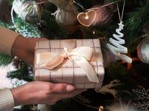 Kvinnlign räcker den hållande julgåvaasken med det vita bandet, filial av granträdet på skinande xmas-bakgrund fotografering för bildbyråer