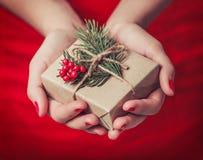 Kvinnlign räcker den hållande julgåvaasken med filialen av granträdet, skinande xmas-bakgrund Feriegåva och garnering royaltyfri foto