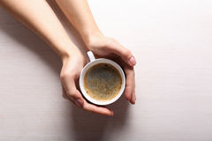 Kvinnlign räcker den hållande koppen kaffe royaltyfri bild