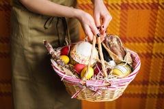 Kvinnlign räcker den hållande korgen med färgrika ägg, kakan, rött vin, hamon eller den knyckiga och torra rökte korven Matgåvaup Royaltyfri Fotografi