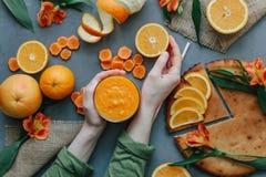 Kvinnlign räcker den hållande orange smoothien som dekoreras med alstroemeria med den orange pajen Fotografering för Bildbyråer