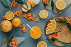 Kvinnlign räcker den hållande orange smoothien som dekoreras med alstroemeria med den orange pajen Arkivfoton
